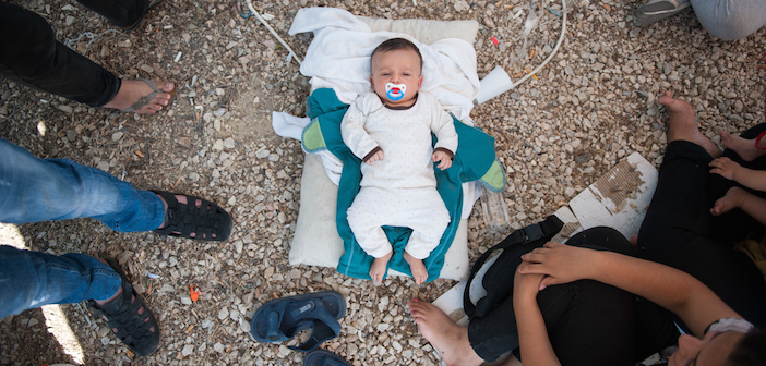 A Syrian newborn lies in the floor of Kara Tepe camp. The family has no milk for the baby and no money to buy.