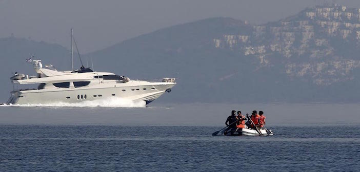 A yacht speeds as refugees paddle an engineless dinghy trying to cross a part of the Aegean sea from the Turkish coast (seen in the background) to the Greek island of Kos August 15, 2015. (Reuters)