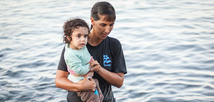 Tali Shaltiel, an Israeli physician, taking a Syrian child from a dinghy that arrived at a beach on the Greek island of Lesbos. (Boaz Arad/IsraAid)