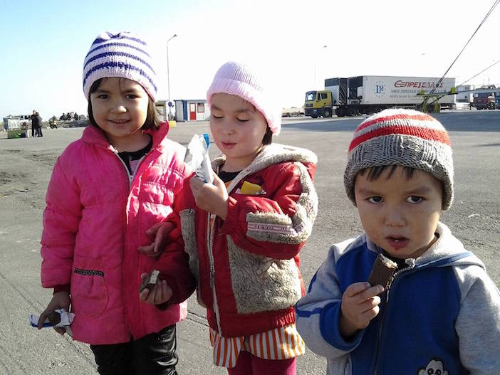 Refugee children with their new hats and scarves, provided by Greek women via the Knitting Solidarity Facebook group