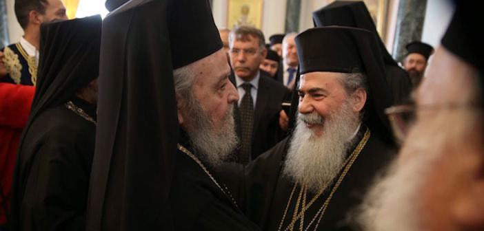 Greek Orthodox Patriarch of Jerusalem Theophilos III (right) is greeted by the former ousted Patriarch of Jerusalem, monk Irineos, March 22, 2016