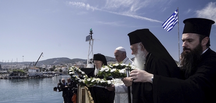 Handout photo shows Pope Francis, Archbishop Ieronimos and Greek Orthodox Ecumenical Patriarch Bartolomew I prepare to throw flower wreaths in the sea in memoriam of the refugees that lost their lives in their effort to reach Europe in Lesbos