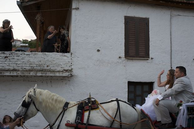 Women toss rice to the couple as they ride by